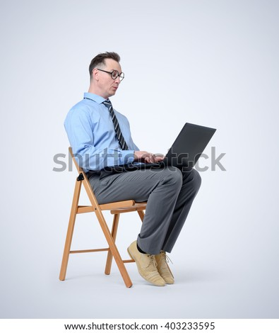 Funny programmer with a laptop sitting in a chair on background