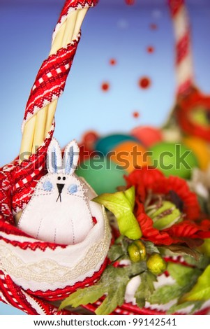 Funny rabbit on easter basket with colored eggs decorated with embroidery and poppies. Shallow depth of field. - stock photo