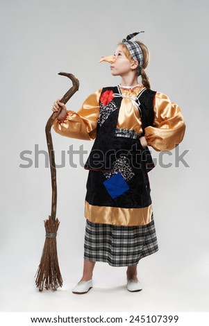 funny red-haired girl in a witch costume with a broom - stock photo