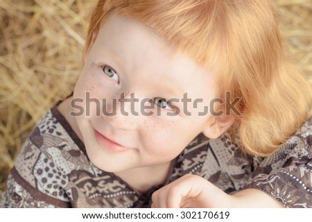 funny red-haired girl with short bangs smiles happily. toned image - stock photo