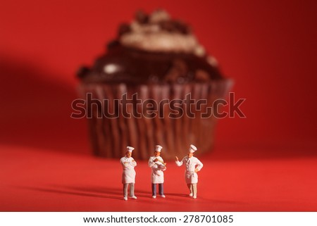 Funny Rendition of Miniature Chefs With Cupcake - stock photo