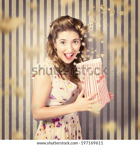 Funny retro pinup portrait of a jumpy woman from 1950 holding vintage snack box with falling popcorn, showing scared expression when watching a scary movie - stock photo