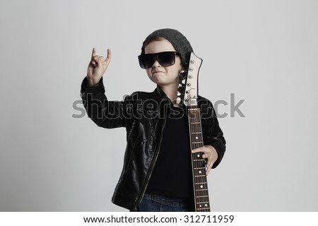 Funny rock child with guitar. fashionable little boy in sunglasses. stylish kid in leather coat. music concept - stock photo