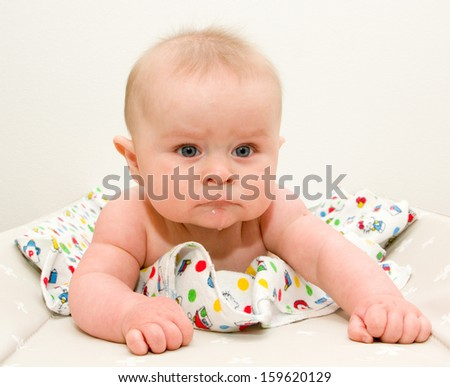 Funny sad toddler laying and watching forward - stock photo