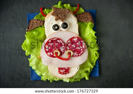 Funny sandwich for child on wooden boards - stock photo