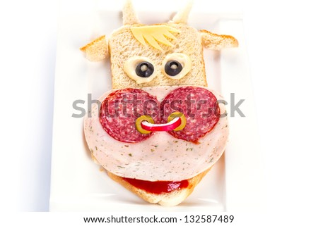 Funny sandwich in the cow shape on the plate - stock photo
