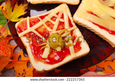 funny sandwich with cheese web and green olives spider for halloween party - stock photo