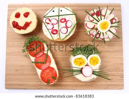 Funny sandwiches for kids on a breadboard - stock photo