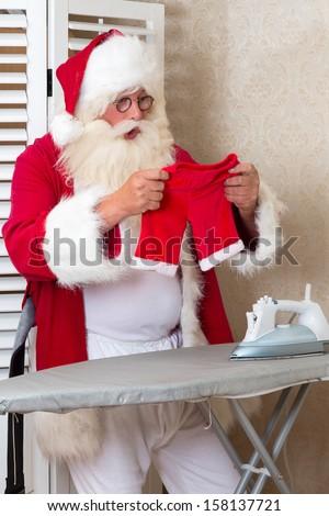 Funny Santa Claus ironing his pants that have shrunk - stock photo