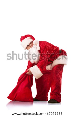 Funny Santa Clause carrying a heavy sack with gifts. Isolated on white.