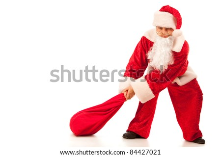 Funny Santa Clause pulling a heavy sack with gifts. Isolated on white.