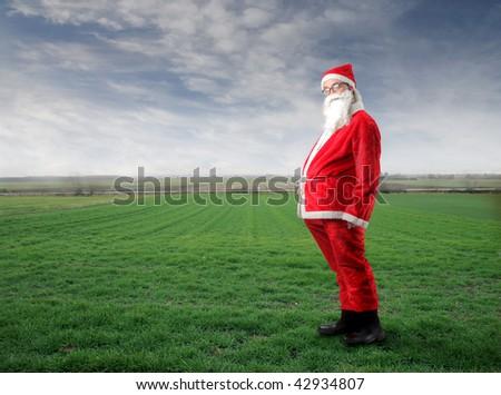 funny santa in a grass field - stock photo
