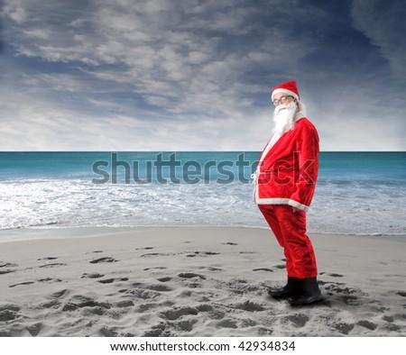 funny santa standing on beach - stock photo