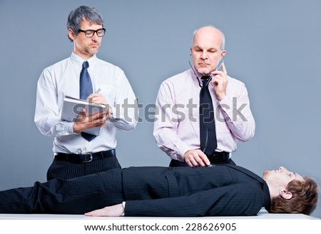 funny scene of two clerks simulating a fake medical examination - stock photo