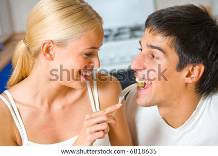 Funny scene of young happy couple playfully eating at kitchen