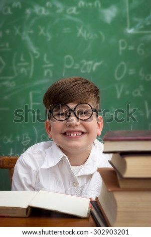 Funny schoolboy  holding book overhead, education concept - stock photo