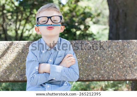 funny schoolboy in glasses being silly ready to go to school, back to school concept - stock photo