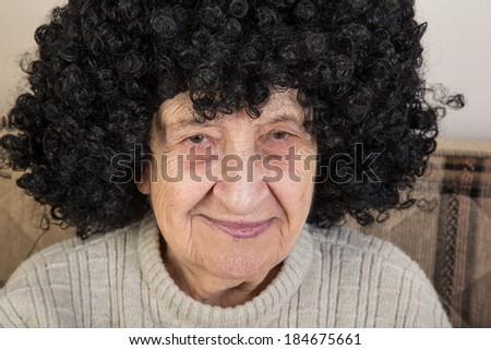 funny senior woman wearing wig - stock photo