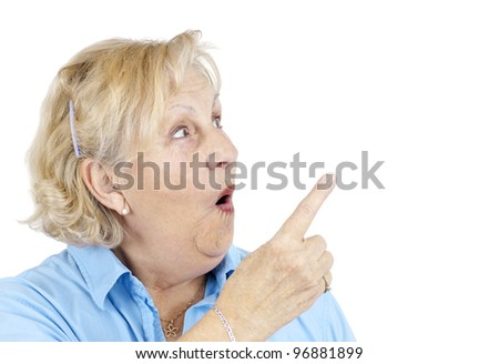 Funny senior woman with surprised face or in shock pointing with her finger at blank space beside her. - stock photo