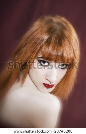 Funny & sexy expressive redhead girl wearing a plastic coat and dress on isolated background