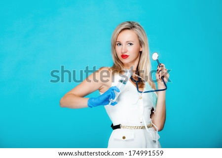Funny sexy girl doctor nurse with syringe stethoscope. Medical person for health insurance. Vivid blue background - stock photo