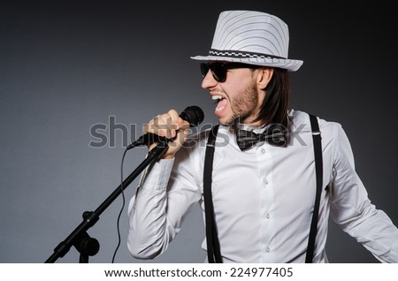 Funny singer with microphone at the concert - stock photo