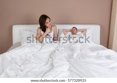 Funny situation in bed. Young couple lying in bed and man is very small but self-confident - stock photo
