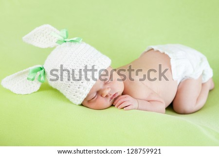 Funny sleeping newborn baby girl over green background - stock photo