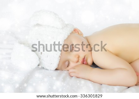 Funny sleeping newborn child. Bunny cap on head of girl. - stock photo