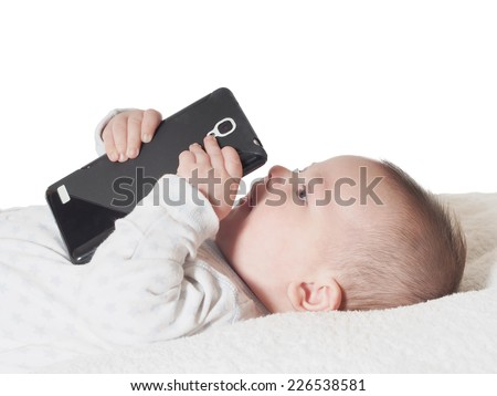 Funny small baby boy holding smart phone in bed - stock photo