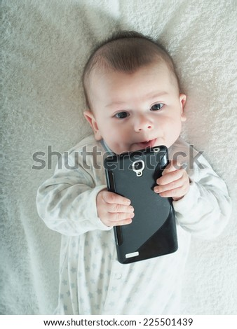 Funny small baby boy holding smartphone in bed - stock photo