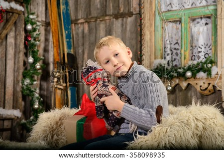 Funny smiling child with Christmas gift in hands. - stock photo