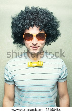 funny smiling guy in afro curly wig with eyeglasses and ribbon bowtie - stock photo