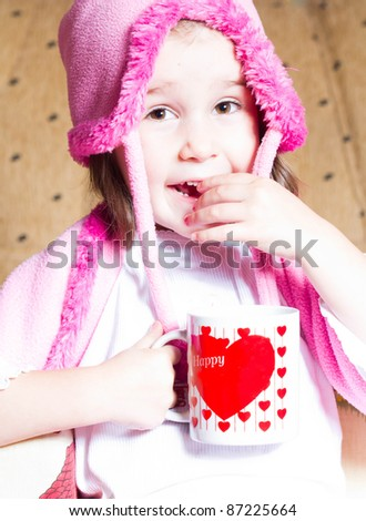 Funny smiling little girl with a cup in hands
