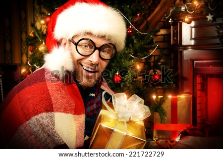 Funny smiling man in Christmas cap and big glasses celebrating Christmas at home. - stock photo