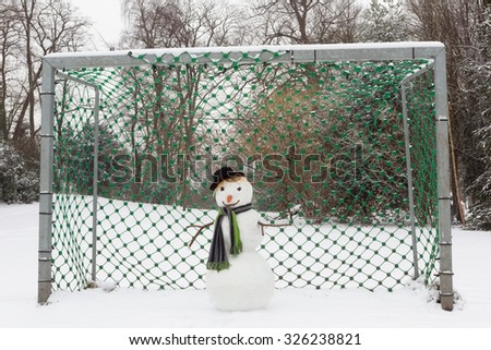 Funny snowman defending the soccer goal in the park - stock photo