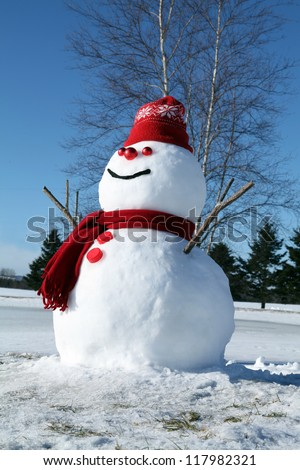 Funny snowman dressed in red on a beautiful winter day - stock photo
