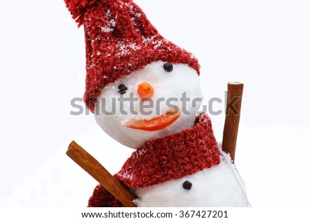Funny snowman wrapped scarf with woolen cap on snow white background, concept of winter season - stock photo