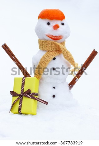 Funny snowman wrapped woolen scarf with tangerine peel on head and gift for Valentines Day, snow white background, concept of winter season - stock photo