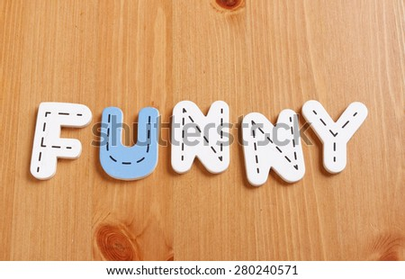 FUNNY, spell by woody puzzle letters with woody background - stock photo