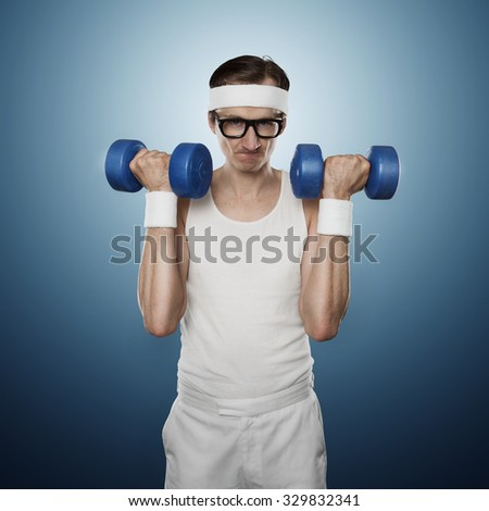 Funny sport nerd lifting weights isolated on blue background - stock photo