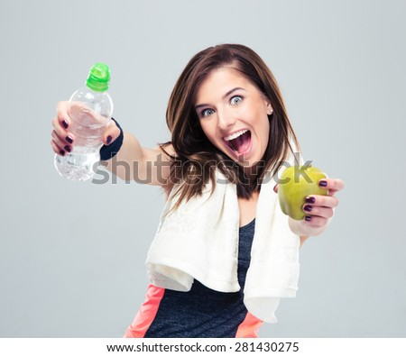 Funny sporty woman holding apple and bottle with water over gray background and looking at camera - stock photo
