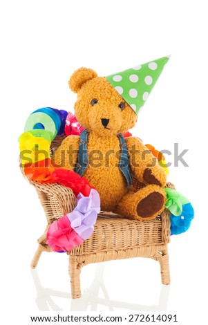 Funny stuffed bear in birthday chair isolated over white background - stock photo