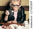 funny stylish blonde girl with great hairdo, glasses, black jacket eating cake in cafe. indoor shot - stock photo