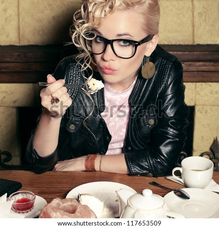 funny stylish blonde girl with great hairdo, glasses, black jacket eating cake in cafe. indoor shot