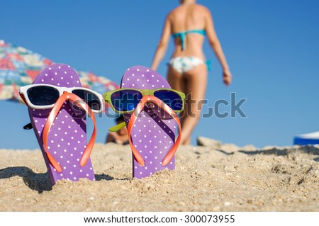 Funny summer flip flops with sunglasses on sandy beach - stock photo