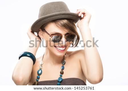 Funny summer portrait of girl in sunglasses, holding her hat with hands