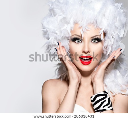 Funny Surprised Woman in white feather wig, holiday make up and accessories. Fashion Model Girl portrait. Creative Makeup and manicure.  Heathers on a head. Hairstyle.  - stock photo