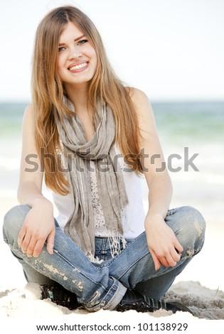 Funny teen girl sitting near the sea. - stock photo