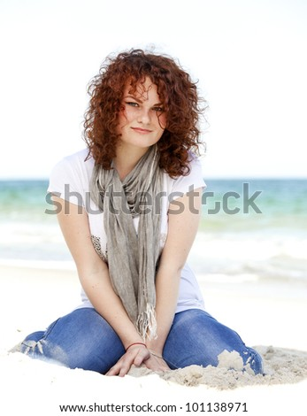 Funny teen girl sitting on the sand at the beach. - stock photo